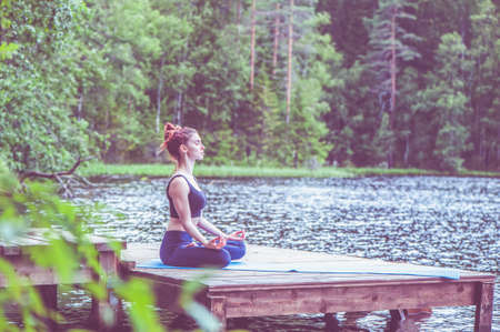 Beautiful girl in a yoga pose on the lake. Lotus position, Padmasana. The concept of appeasement, healthy lifestyle. Panoramic view