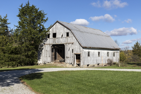 White barn with a blue sky and clouds.