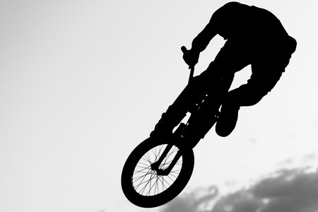 radical: Silhouette of a boy performing a radical jump Stock Photo