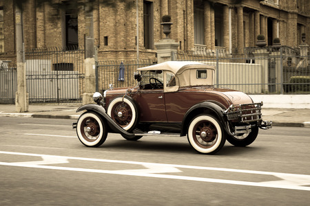 jalopy: Ford Model A Deluxe cabriolet in front of a British brick building Editorial