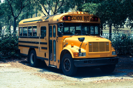 School Bus parked in the shade next to the school Banco de Imagens