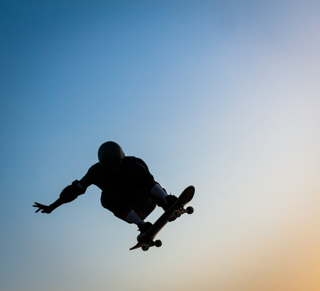 kneepad: skateboarder jumping with blue sky in background