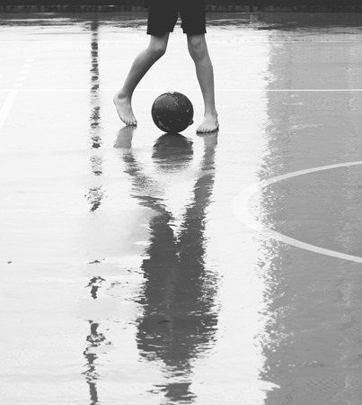 sports club: Boy barefoot playing soccer in the rain.