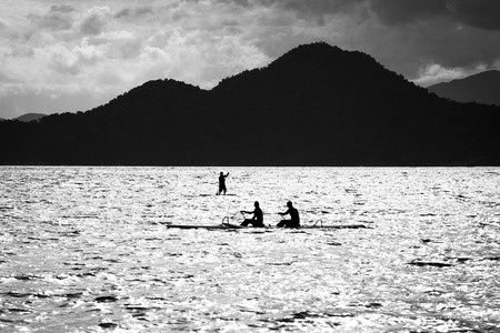 outrigger: Double paddling on a outrigger canoe and stand up paddle in the background Stock Photo