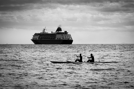 outrigger: Double paddling on a outrigger canoe with a transatlantic in the backgroud
