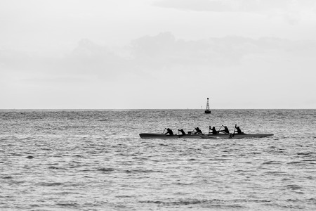 Six paddlers in a outrigger canoe Stock Photo