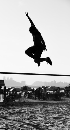 slacker: Brazilian teenager playing slackline on the beach in Santos, Brazil Stock Photo