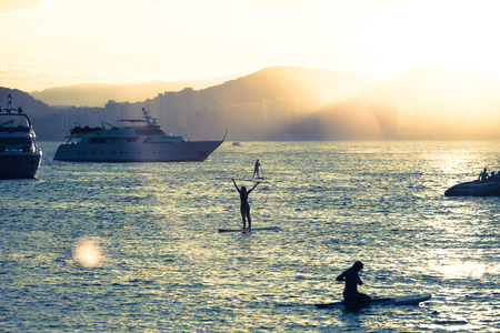 Yachts and people practicing stand up paddle, during the sunset, in Guaruja, Brazil Imagens