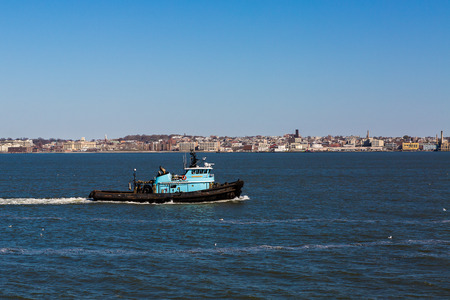 Blue tugboat entering the port of New York, USA.