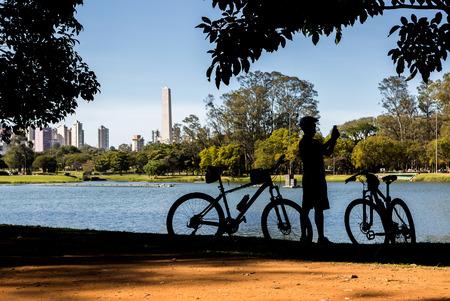 サイクリスト、ブラジル、サンパウロのイビラプエラ公園内の湖で写真を撮るします。