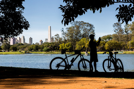 Cyclist by the lake in Ibirapuera Park, Sao Paulo, Brazil, taking photos.