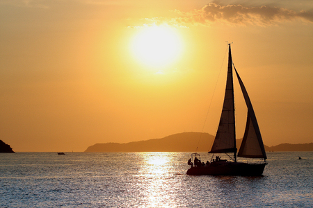Sailboat sailing during summer sunset, in Santos, Brazil.