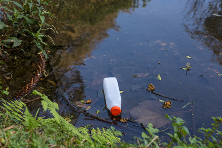 The principle of water pollution, plastic bottle on river surface Фото со стока