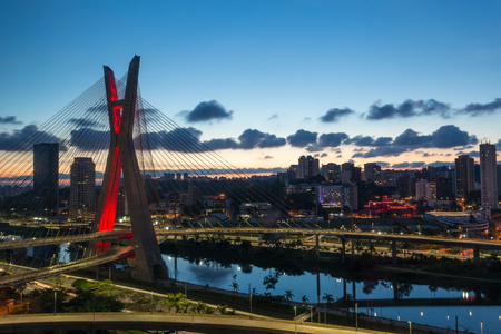 The Octavio Frias de Oliveira bridge is a cable-stayed bridge in Sao Paulo, Brazil over the Pinheiros River at sunset.
