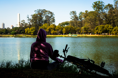 Unidentified old woman, sitting in lotus position, meditates after a bike ride. Stock fotó