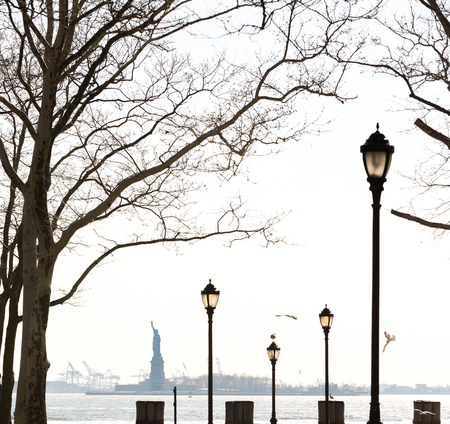 View of the Statue of Liberty from Battery Park with the New York Harbor in the background. Stock Photo