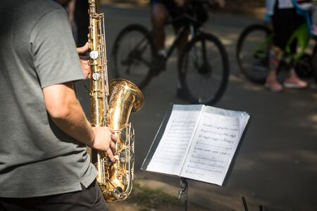 Street musician playing saxophone on a sunny day.