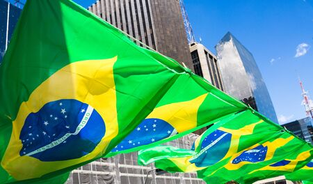 Flags of Brazil fluttering in the wind at a popular demonstration on Avenida Paulista, Sao Paulo, Brazil.