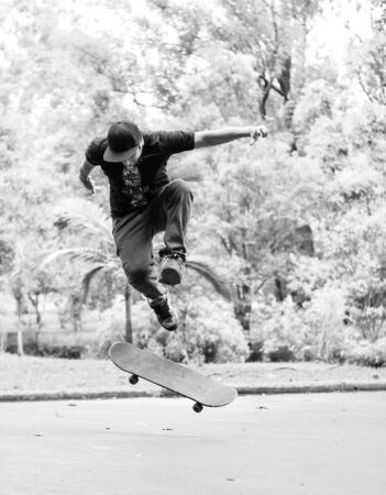 Boy practicing street skateboard, freestyle in black and white. Фото со стока