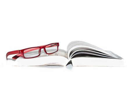 Book and reading glasses on a white background.