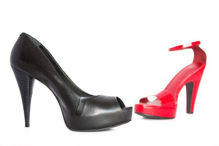 One black high heel and one red heel on a white background. Stock fotó