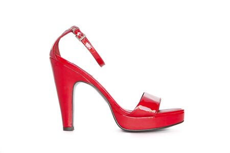 Red high-heeled womens shoe on a white background.