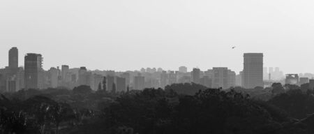 Sao Paulo skyline photographed in black and white with a helicopter taking off from a building on Avenida Faria Lima.