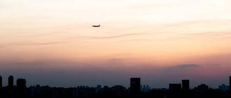 Airplane getting ready to land in Sao Paulo during a beautiful sunset.