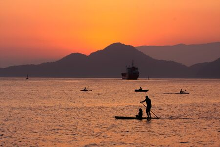 Sunset in Santos, Brazil. People having their leisure time paddling while a ship leaves port. Stock fotó