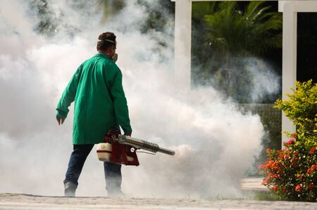 Man pesting gardens to fight the Dengue and Yellow fever mosquito in Brazil. Bug fumigation.