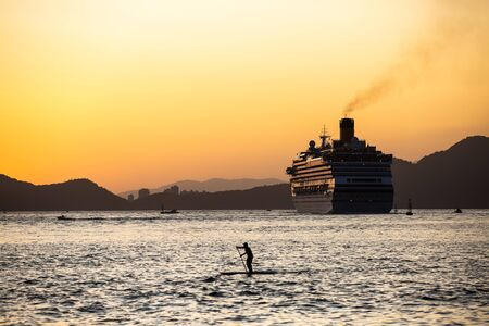 A cruise ship leaving the port of Santos, Brazil, during a beautiful summer sunset.