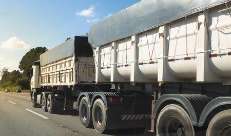 Double semi-trailer truck  at the interurban road. Stock Photo