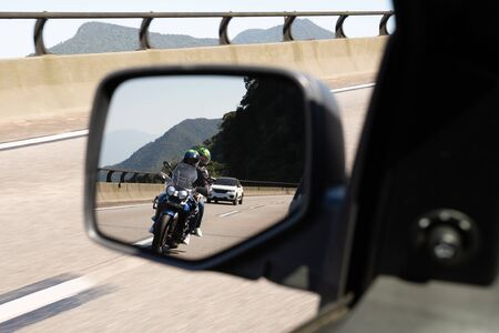 Car rear view mirror with the image of a biker approaching to overtake.
