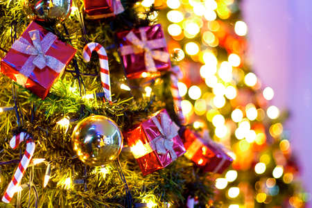 Background with Christmas tree with colorful bokeh in the background.