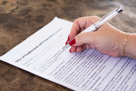 Woman signing employment contract on a marble table. Stock Photo