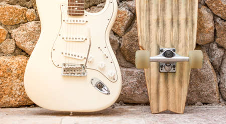 Body of a guitar and skateboard leaning against a stone wall. Stock Photo