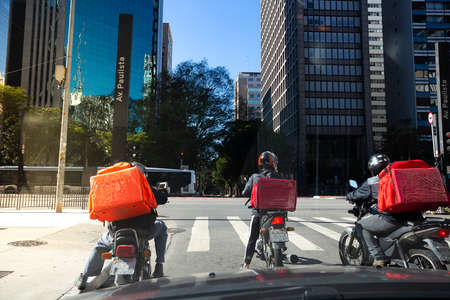 Three motorcycle couriers stopped at Av. Paulista, in São Paulo, during the pandemic period.