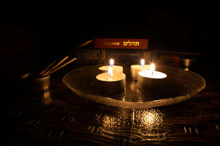 Candles lit on the day of Yom Kippur with the book of Psalms and the Bible in the background. Imagens