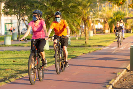 Santos, Brazil. May 09, 2020. Cyclists pedaling wearing protective masks against Coronavirus on the bike path in the city of Santos, during the pandemic.