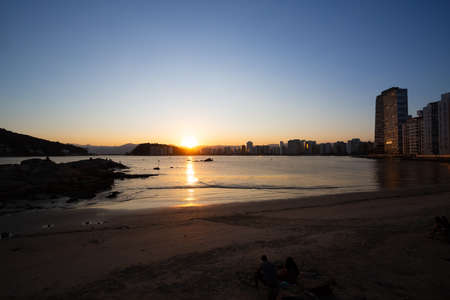 Tourists watch a beautiful sunset in the bay of Sao Vicente, Brazil.