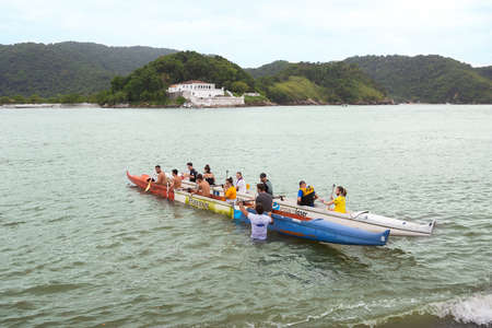 Santos, Brazil. February 07, 2021. Tourists listening to the latest instructions before a Hawaiian canoe ride off the coast of Santos. Editorial