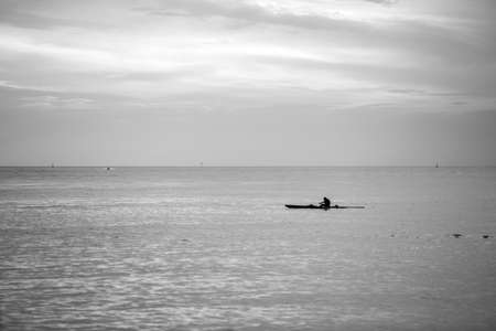 Man paddling a Hawaiian canoe during a late afternoon in Santos, Brazil.