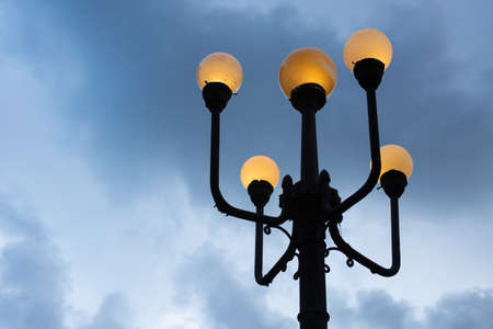 Old lamp in the city of Santos, Brazil, lighting up in the evening. Imagens
