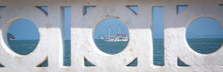 Tourist boat framed in the span of the wall that is the hallmark of the city of Santos.