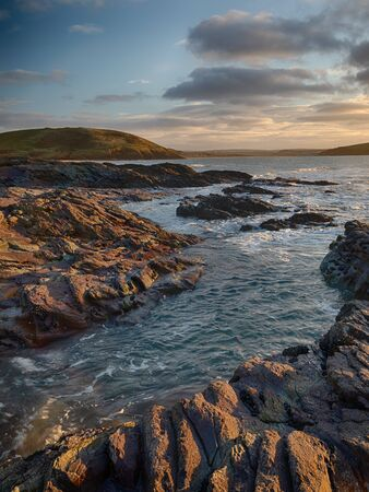 The rocks around Daymer illuminated by the setting sun. Brea Hill in the background and Padstow off in the distance.
