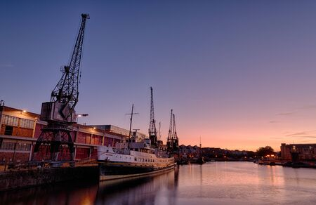 Bristols floating harbour at sunset. In the foreground is a ship, the Balmoral. Next to it are the M-Shed cranes, disappearing down quayside.