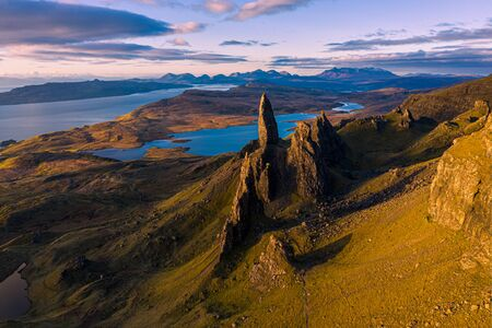 An aerial view from the Storr of the Old Man of Storr with the Black Cuillin mountains in the distance. The sun has only just risen above the horizon on a beautiful May morning on the Isle of Skye, Scotland, UK.