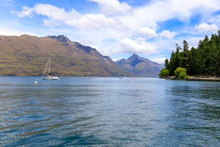 A sailing boat on Lake Wakatipu with mountains in the background. Queenstown, New Zealand. Imagens