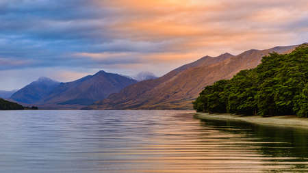 North Mavora Lake surrounded by forests with mountains in the background at sunset on a cloudy day. Imagens