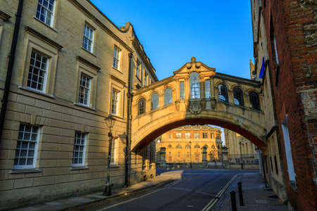 Hertford Bridge, Bridge of Sighs, in Oxford at sunrise with Sheldonian Theatre behind it and no people around, early in the morning on a clear day with blue sky. Oxford, England, UK. Stock Photo